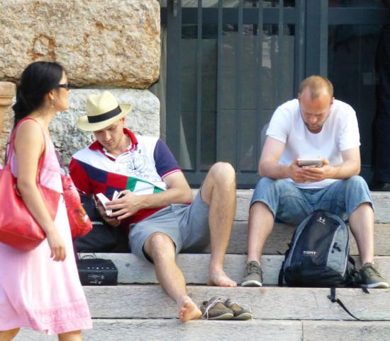 turisti che leggono sui gradini della gran guardia verona