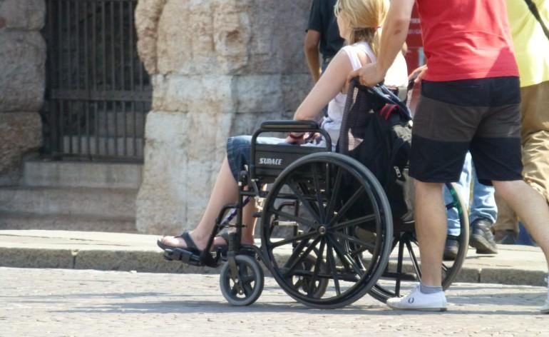 donna in carrozzina con arena di verona sullo sfondo