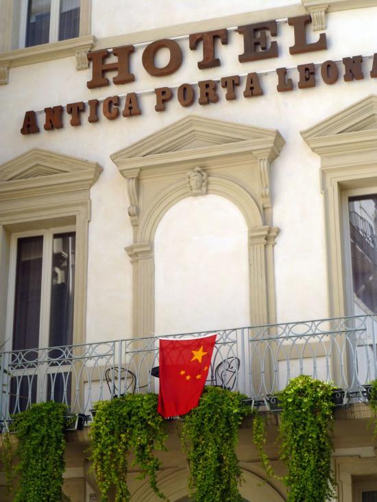 la bandiera cinese sventola dal balcone dell'hotel antica porta leoni