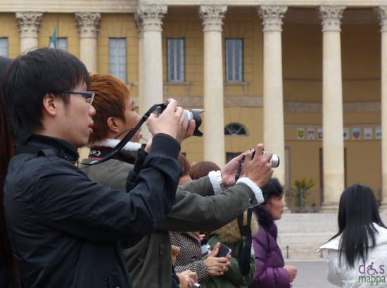 a verona turisti asiatici fotografano piazza bra