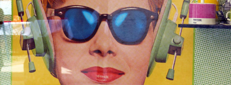 poster nelle vetrine di quality living in via cairoli con donna anni '50 con occhiali da sole e cuffie