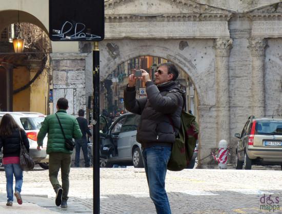 verona, turista fotografa i palazzi in corso cavour, sullo sfondo porta borsari