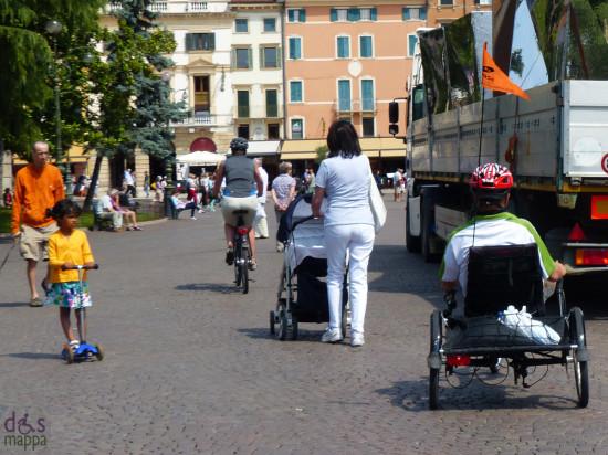 monopattino, bicicletta, carrozzina, camion con scenografie aida, ragazzo disabile su hanbike in piazza bra a verona