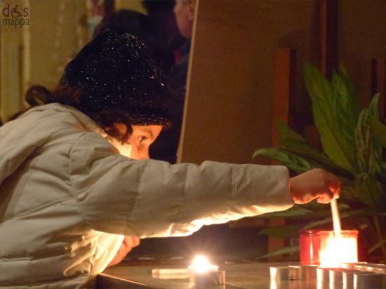 Bambina accende una candela alla Chiesa di San Nicolò all'Arena