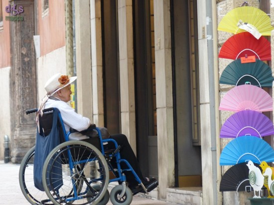 Signora anziana in carrozzina in attesa fuori da un negozio con lo scalino in via Stella a Verona