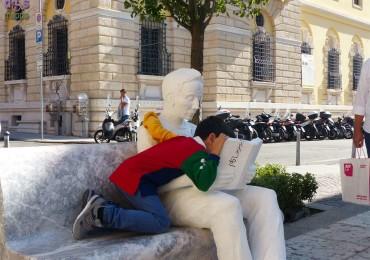 Bambino con istallazione La lettura di Enrico Pasuale per Marmomacc and the City Piazzetta Navona Verona