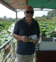 Il Signor Francesco, uno dei barcaioli del Mincio, testimone di accessibilità per dismappa tra i fiori di loto sulla barca accessibile ai visitatori in sedia a rotelle.