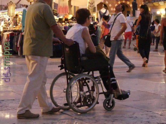 Carrozzina di cortesia senza possibilità di spinta autonoma, turisti in Piazza delle Erbe a Verona