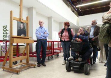 I restauratori dei quadri rubati a Castelvecchio spiegano i lavori di restauro e conservazione ai visitatori, tra cui uomo con disabilità in sedia a rotelle tecnologica